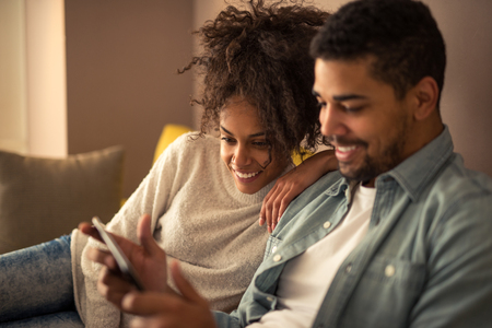 tv show: African american couple watching favorite TV show on a tablet. Stock Photo