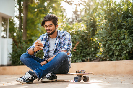 skateboarder: Young teenager texting on a mobile phone. Stock Photo