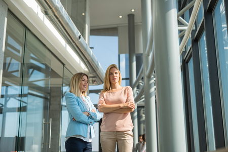Two female colleagues talking about business in a modern office.