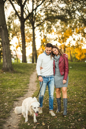 Couple cuddling while walking a dog in the park.