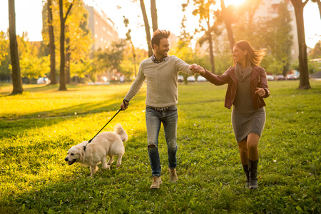 holding hands while walking: Couple holding hands while walking the dog.