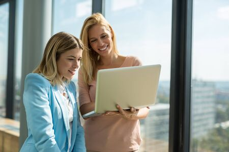 sucessful: Happy female business team working together on a laptop. Stock Photo