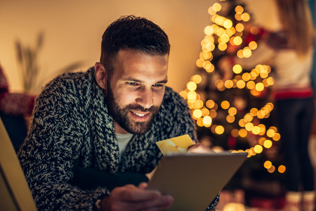 tablet: Handsome man holding a credit card and shopping on a tablet.