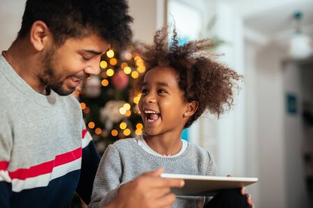 Cute girl using tablet with dad at home. Stock Photo