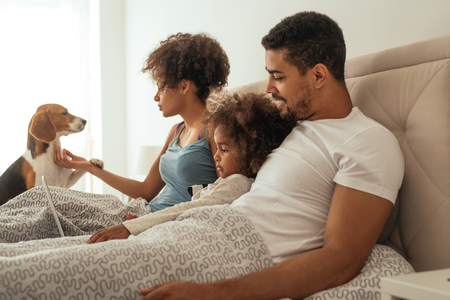 Happy family spending time together with their dog in a bed.
