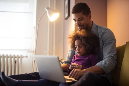female child: African american dad and his daughter using laptop together.