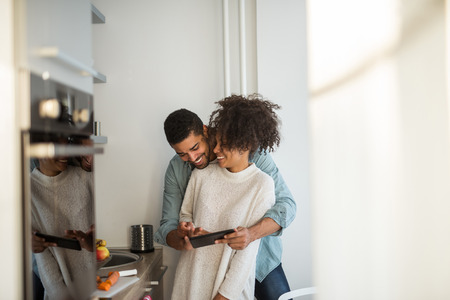 African american couple using tablet together in the kitchen.