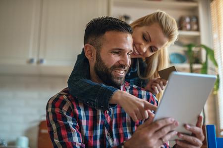spending money: Couple spending money online on the internet.