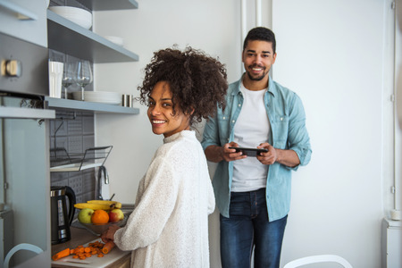 married couples: Handsome african american man is using tablet while girl is cooking.