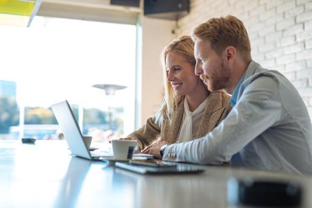 Collega's die aan een computer in een koffiewinkel samenwerken. Stockfoto