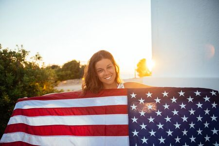 Proud woman showing the USA flag at sunset.