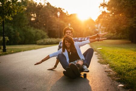 urban people: Happy couple enjoying ride on a long board.