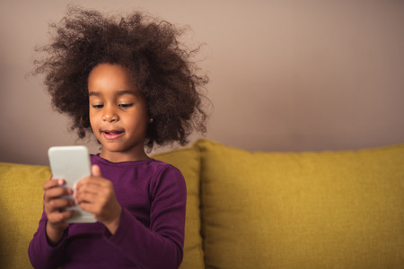 Curious little girl playing games on her mobile phone indoors.