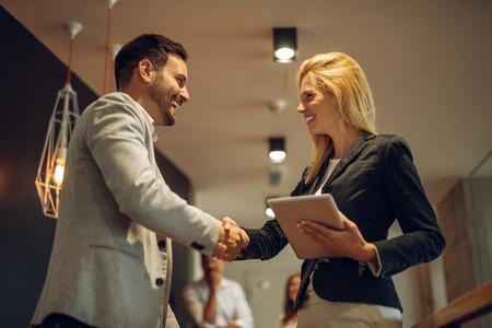 Gelukkig collega's handshaking tijdens een bijeenkomst in het kantoor.
