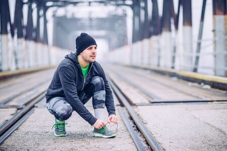shoelace: Handsome man tying a shoelace while runnning outdoors. Stock Photo