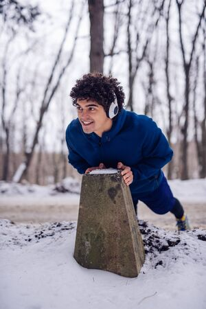 Portrait of a young athlete stretching on his morning workout routine in the woods while listening to the music.