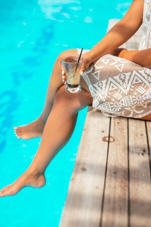 Close up portrait of a woman holding a cocktail and sitting by the pool with her legs in water. Stock Photo