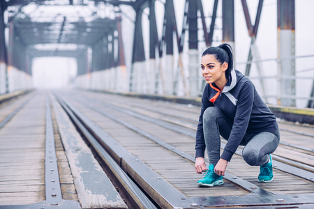 shoelace: Handsome woman tying a shoelace while runnning outdoors. Stock Photo