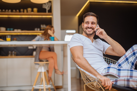 domicile: Handsome male talking on the phone at the apartment. The girl is sitting in the kitchen behind him. Stock Photo