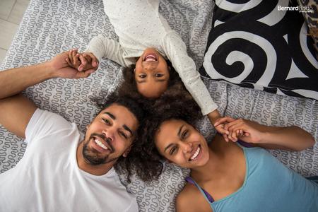 Close-up portret van boven van gelukkige Afro-Amerikaanse familie in de slaapkamer.