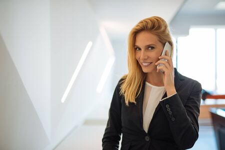 negotiating: Businesswoman negotiating on the phone in the company.