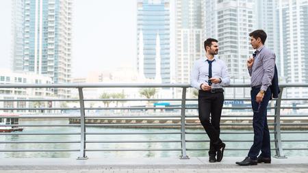 Portret van twee zakenlieden praten over het nieuwe project die buiten in de buurt van het hek aan de rivier. Stockfoto