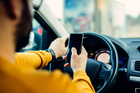 Shot of a handsome man using mobile phone while driving.