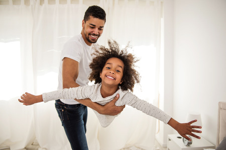 African american father and daughter playing indoors.