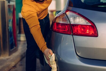 Shot of a male cleaning his car with a cloth outdoors.