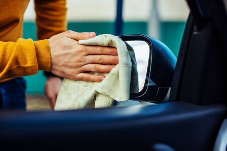 Shot of a male hand cleaning the rear view mirror on his car. Stock Photo