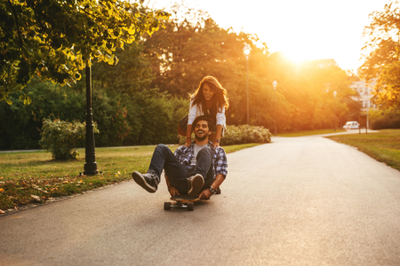 Shot of a happy couple having fun skateboarding outdoors by the sunset. 版權商用圖片 - 73623854