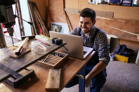 Portrait of a smiling young carpenter sitting at the table and using laptop in workshop.