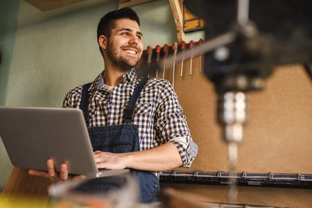 워크샵에서 직장에서 노트북을 사용 하여 웃는 목수의 총. 스톡 콘텐츠