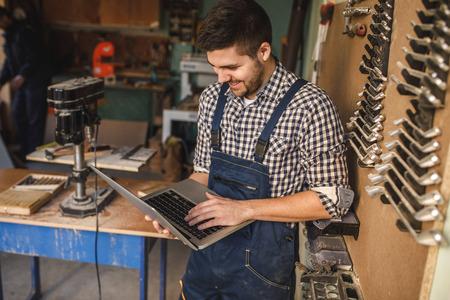 若い大工彼のワーク ショップでノート パソコンでの作業です。