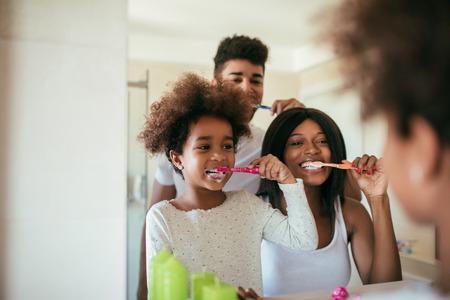 Photo d'une famille afro-américaine heureuse qui se lave les dents pendant la routine quotidienne du matin. Banque d'images - 75068889
