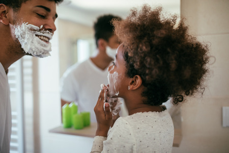Photo of african american father and daughter having fun with shaving foam in the bathroom. Stock Photo