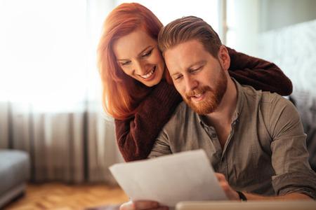 Foto van een gelukkig paar die financiën thuis doen. Stockfoto