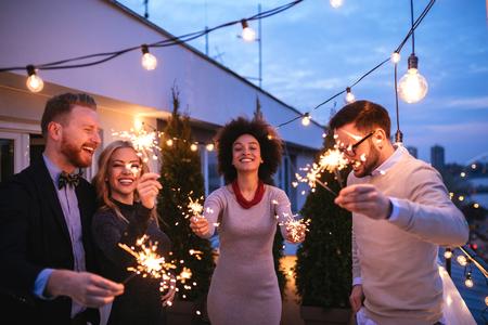 Amis jouissant d'une fête sur le toit et dansent avec des étincelles dans les mains. Banque d'images - 75465968