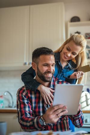 젊은 부부는 집에서 온라인 쇼핑. 남자는 디지털 태블릿을 잡고 그리고 여자는 신용 카드를 잡고있다. 그들은 모두 웃고있다.