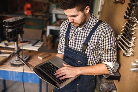 그의 워크샵 직장에서 노트북을 사용하여 젊은 carpenter 초상화.