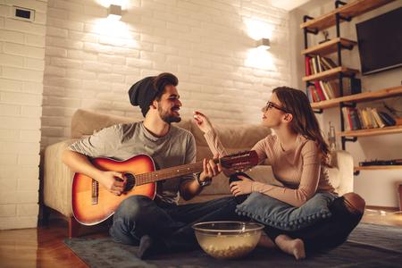 그의 여자 친구에 기타를 일부 음악 재생 잘 생긴 남자.