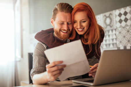 Photo of young couple embracing trough work at home. Standard-Bild