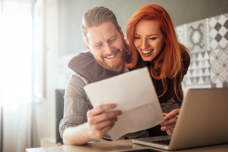 Fotografie pozitivního mladého páru, který obejme a vypočítává účty doma.