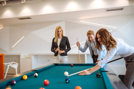 Group of young colleagues playing billiard at work. Stock Photo
