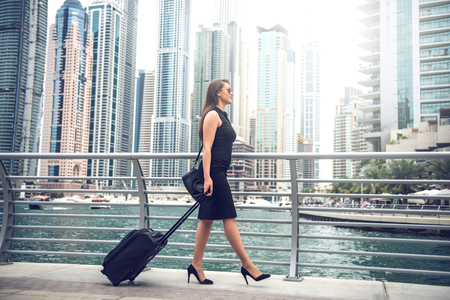woman handle success: Full length portrait of a confident businesswoman pulling suitcase in a big city.