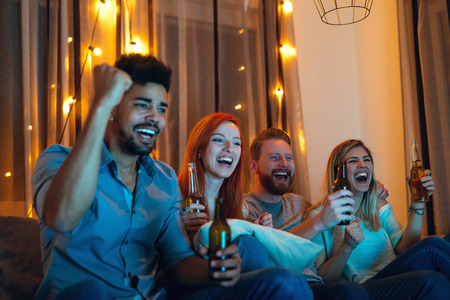 couple on couch: Shot of happy and satisfied friends enjoying watching a game at home. Stock Photo
