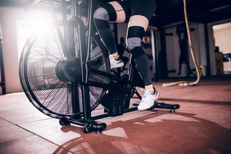 Shot of athlete woman exercising on assault air bike. Stock Photo