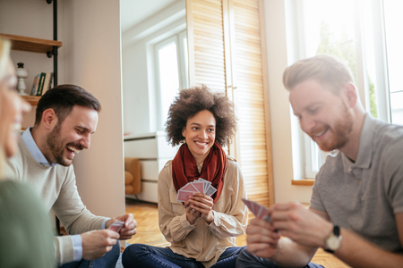 Foto van gelukkige vrienden speelkaarten en samen opknoping.