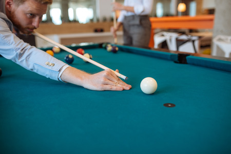 Handsome ginger man playing billiard in the office. Stock Photo