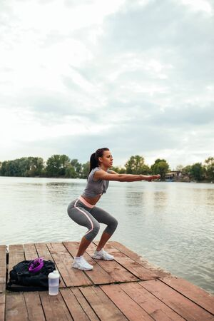 Full length portrait of an athlete woman doing squats outdoors in the nature. Stock Photo